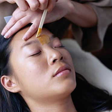 Waxing to eliminate hair between eyebrows